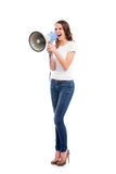 A young and attractive Caucasian woman screaming on the megaphone. A young and attractive Caucasian woman in stylish jeans screaming on the megaphone. The image stock image