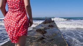 Young attractive caucasian woman walking on the pier wearing red dress. Barefoot legs walking towards the sea on the pier. Slow mo stock video