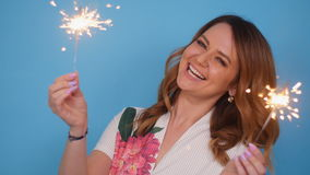 Young attractive celebrating woman holding sparkles. Portrait of young attractive celebrating woman holding sparkles stock footage