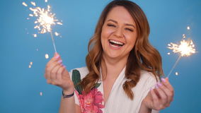 Young attractive celebrating woman holding sparkles. Portrait of young attractive celebrating woman holding sparkles stock video