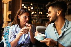 Young attractive couple on date in coffee shop. Young attractive cheerful couple on date in coffee shop stock images