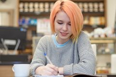Young, attractive, cheerful, friendly girl student sitting in a stock photos