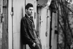 Black and white art monochrome photography. Young attractive cheerful man with dark hair with a beard wearing a shirt and a black jacket on the street. Male Stock Photo