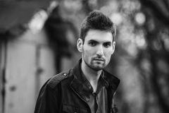 Black and white art monochrome photography. Young attractive cheerful man with dark hair with a beard wearing a shirt and a black jacket on the street. Male Royalty Free Stock Images