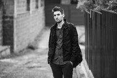 Black and white art monochrome photography. Young attractive cheerful man with dark hair with a beard wearing a shirt and a black jacket on the street. Male Stock Photography