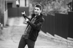 Black and white art monochrome photography. Young attractive cheerful man with dark hair with a beard wearing a shirt and a black jacket on the street. Male Royalty Free Stock Photo