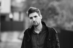 Black and white art monochrome photography. Young attractive cheerful man with dark hair with a beard wearing a shirt and a black jacket on the street. Male Royalty Free Stock Image