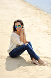 Young attractive cheerful woman sitting on a sand Stock Image