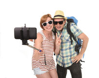 Young attractive and chic American couple taking selfie photo with mobile phone isolated on white Stock Photography