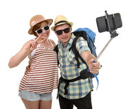 Young attractive and chic American couple taking selfie photo with mobile phone isolated on white Royalty Free Stock Image