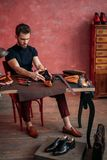 Young attractive cobbler measuring the leather for shoe. Measurement, full length photo stock photography