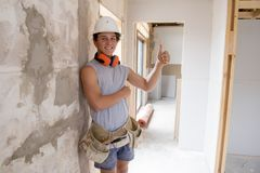 Young attractive and confident builder and constructor job trainee learning and working at industrial renovation site blue collar. Young attractive and confident stock photo
