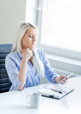 Young, attractive and confident business woman working in office Royalty Free Stock Image