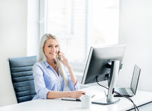 Young, attractive and confident business woman working in office Stock Photography
