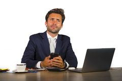 Young attractive and confident businessman in suit working at corporate company office computer desk on white background royalty free stock photo