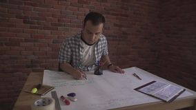 Young attractive confident concentrated man in plaid shirt working on business project thinking sitting by wooden table. People working on project in business stock video footage