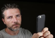 Young attractive and confident white man with blue eyes using online dating app or internet social media on mobile phone isolated. Close up face portrait of royalty free stock photography