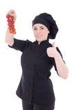 Young attractive cook woman in black uniform with tomato isolate Royalty Free Stock Photo