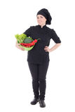 Young attractive cook woman in black uniform with vegetables iso Stock Image