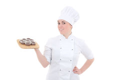 Young attractive cook woman in uniform with chocolate muffins is Royalty Free Stock Image