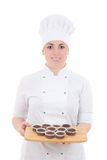 Young attractive cook woman in uniform with muffins isolated on Stock Photos