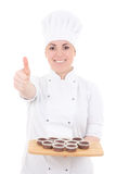 Young attractive cook woman in uniform with muffins thumbs up is Royalty Free Stock Photography
