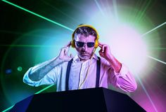 Young attractive and cool DJ in shirt and suspenders remixing music at night club using headphones in party strobo and laser. Lights background in clubbing and royalty free stock photo