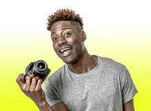 Young attractive and cool happy black afro American man holding digital reflex photo camera smiling excited isolated on yellow bac stock image