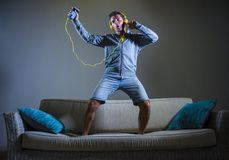 Young attractive and cool happy man listening to music with yellow headphones jumped on top of home sofa couch dancing internet so. Ng excited in trance holding Stock Image