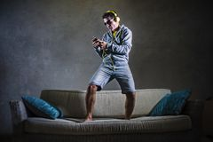 Young attractive and cool happy man listening to music with yellow headphones jumped on top of home sofa couch dancing internet so. Ng excited in trance holding Royalty Free Stock Image