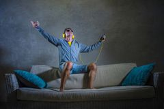 Young attractive and cool happy man listening to techno music with yellow headphones jumped on top of home sofa couch dancing inte. Rnet song excited in trance Stock Photography