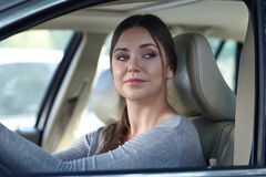 Young attractive coquettish caucasian woman in car flirting with pedestrian or other driver. Trendy and confident diverse woman be stock photos