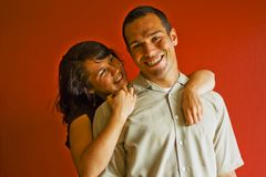 Young Attractive Couple. Smiling and happy with each other against a red background Stock Images