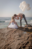 Young attractive couple at beach on rocks with white balloons Royalty Free Stock Images