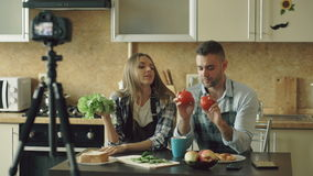 Young attractive couple bloggers shooting video food blog about cooking on dslr camera in the kitchen stock video
