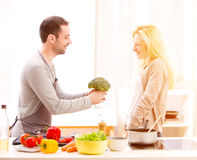 Young attractive couple cooking in a kitchen Stock Images