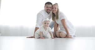 Young attractive couple and cute baby sit on white floor and look at camera.