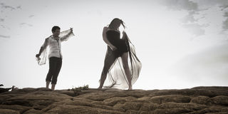 Young attractive couple dancing outdoors on beach rocks Stock Images