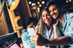 Young attractive couple on date in coffee shop. Young attractive cheerful couple on date in coffee shop Royalty Free Stock Image