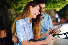 Young attractive couple on date sitting on bench Stock Photo