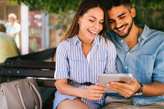 Young attractive couple on date sitting on bench Stock Images