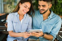 Young attractive couple on date sitting on bench Stock Image
