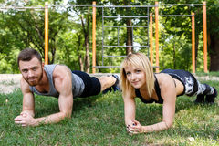 Young attractive couple doing exercise plank in park together. Stock Photos