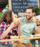 Young attractive couple eating hamburgers against food truck with lens flare in background