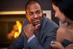 Young attractive couple by fireplace talking Royalty Free Stock Photos