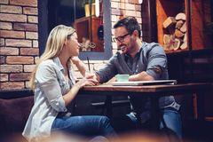 Young attractive couple flirting in cafe. Young attractive couple flirting in new cafe royalty free stock photography