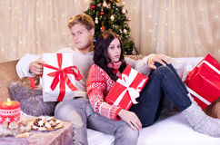 Young attractive couple  in front of christmas tree in bad mood Royalty Free Stock Photos