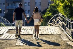 Young and attractive couple is going along the bridge in park. Royalty Free Stock Photo