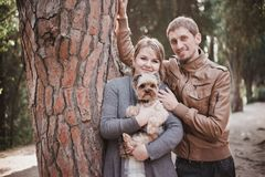 Young attractive couple going for a walk with their dog. In a park Stock Images