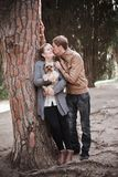 Young attractive couple going for a walk with their dog. In a park Royalty Free Stock Photography